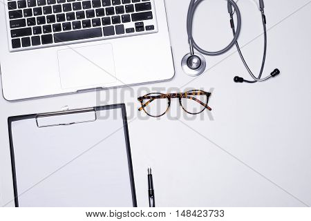 The Top View Of Doctor Desktop With Stethoscope, Clipboard With Medical Records Form And Computer La