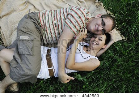 happy young cuple lie in green gras and flirting while listening music and have romantic time and beginning of new love
