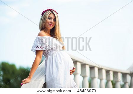 Beautiful young pregnant woman in a white dress standing on the background of the stairs.
