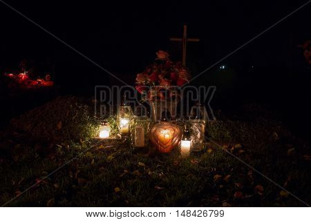 Votive Candles Lantern Burning On The Graves In Slovak Cemetery At Night Time. All Saints' Day. Sole