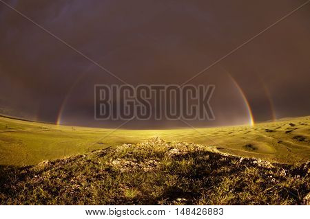 Rainbow on the dark sky background over a meadow