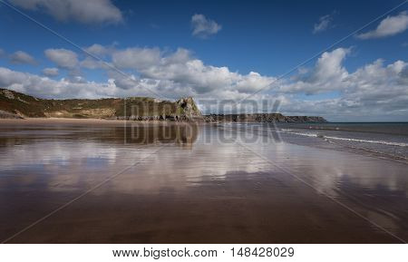 Low tide creates a reflection of the Great Tor in South Gower, South Wales.