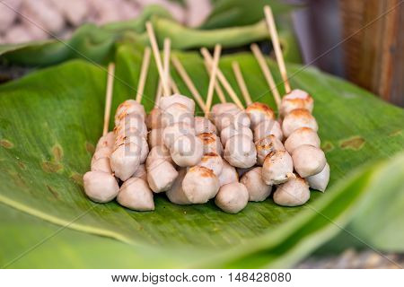 Close-up detail of a stack of pork ball skewers on banana leaves at a street food stall. Travel and cuisine concept.