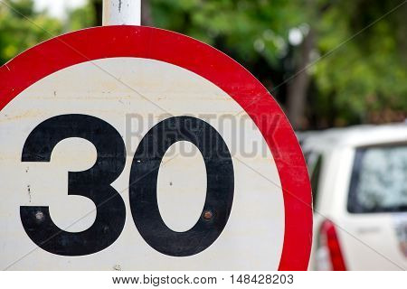 Close-up detail of a circular 30 kilometers per hour speed limit sign in a residential area. Law enforcement concept.