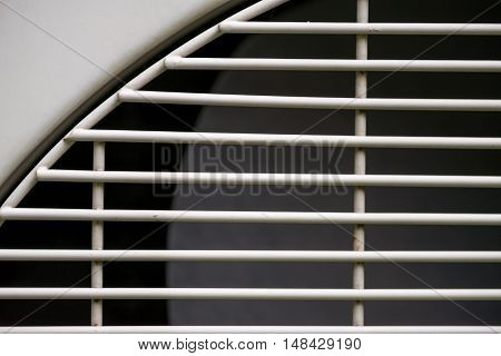 Close-up detail of the metal grille covering an industrial grade condenser used for processes such as distillation. Industry and engineering concept.