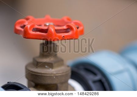 Close-up detail of a red gas valve handle for emergency shutoffs. They are used in various factories and home plumbing systems. Industry and engineering concept.
