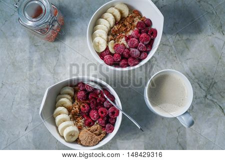 Oatmeal with raspberries, banana, nut butter, hemp seeds and goji berries, coffee cup on granite countertop/ vegan.