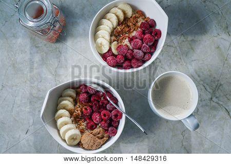 Oatmeal with raspberries, banana, nut butter, hemp seeds and goji berries, coffee cup on granite countertop/ vegan.