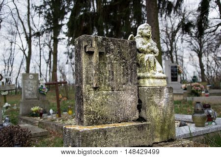 Graves tombstones and crucifixes on traditional cemetery. Statue of an angel on old tomb stone in graveyard. All Saints' Day. All Souls' Day. Gravestones in village Tvrdomestice Slovakia