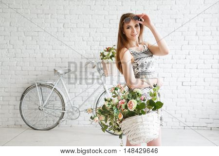 Beautiful young woman with bike on backgraund and bascket full of flowers
