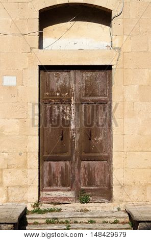 Ancient wooden front door in a crumbling building