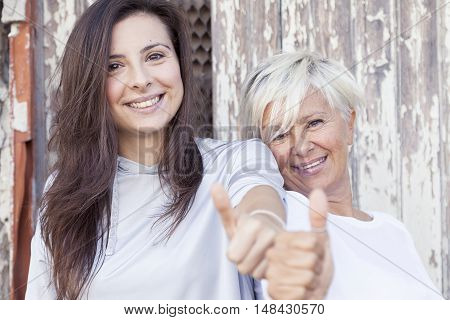 Pretty Mother And Adult Daughter Make The Sign Of Thumbs Up Outdoor