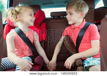Happy Kids, Adorable Girl With Her Brother Sitting Together In Modern Car Locked With Safety Belts E