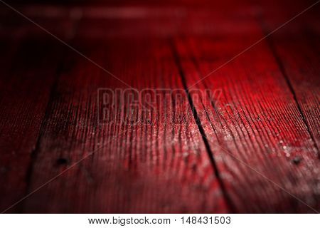 Textural image: red-lighted surface of wooden board