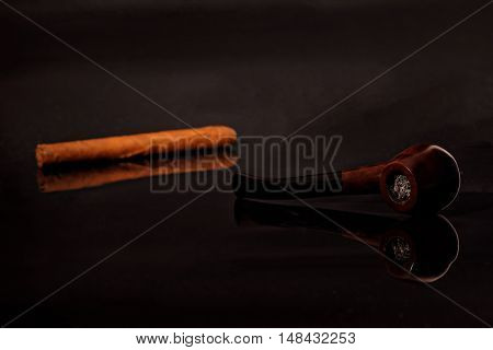 Brier smoking pipe and cigar with reflection isolated on black background