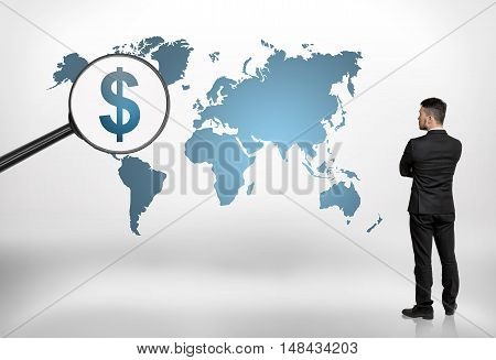 Back view of a businessman looking at world map with big magnifier enlarging dollar sign on it. Global business. Perspectives and opportunities. North America.