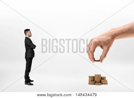 Side view of a businessman looking at big man's hand making stacks of golden coins isolated on white background. Prosperity and wealth. Saving money.