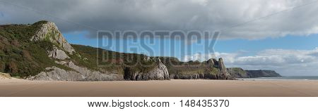 Panorama of the cliffs on Oxwich Bay and Nicolaston Burrows featuring the Great Tor on the Gower peninsular, South Wales.