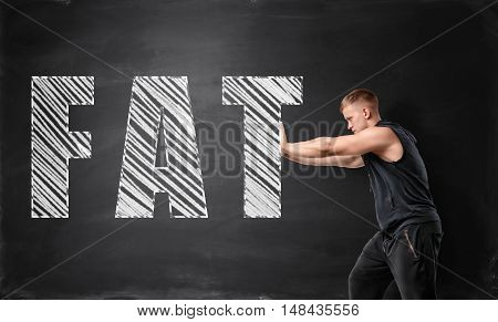 Muscled young man pushing big drawn 'fat' word by both hands on the background of a blackboard. Losing weight and fat burning. Bodybuilding and self-improvement.