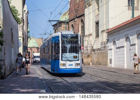 POLAND, KRAKOW - MAY 27, 2016: Tram Bombardier Flexity Classic in the historic part of Krakow. Total in Krakow more than 90 kilometers of tram tracks and 24 routes.