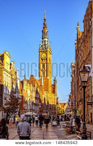 GDANSK, POLAND - SEPTEMBER 18, 2016: Peoples on Long Street one of Europe's most beautiful town with renaissance building of the former Town Hall in Gdansk. Old Town in Gdansk is a tourist attraction for visitors.