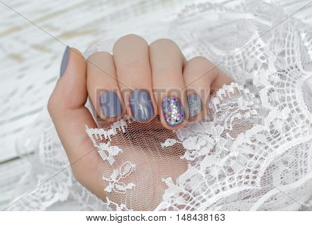Female hand with gray nail design holding lace