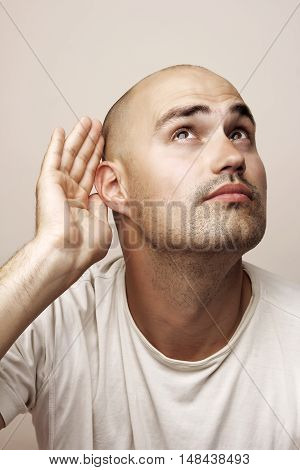 Head shot of  bald man in white t-shirt facial expressions series, eavesdropping.