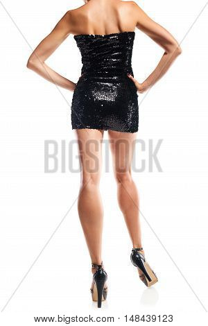 Cropped image of back view woman legs in black sequinned mini dress, white background