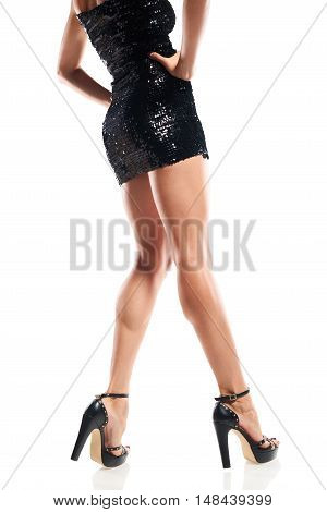 Cropped image of woman legs in black sequinned mini dress, white background