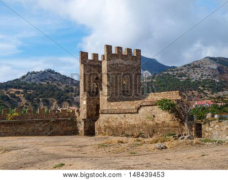 Fortress wall and majestic stone gates of the fortress against the backdrop of mountain scenery in Sudak in Crimea