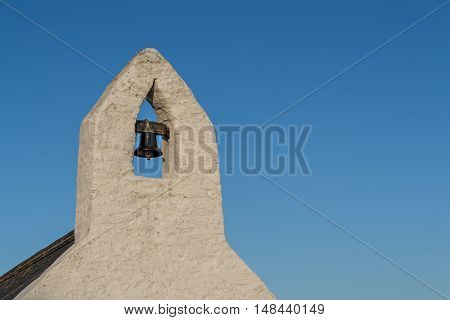 Small bell tower with a bell of a Welsh country chapel, against a deep blue sky