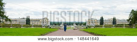 Panorama of the Palace and park ensemble Arkhangelskoye in Moscow with the walking woman