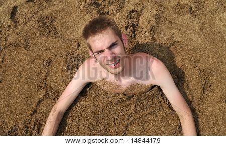 Young Man Buried In The Sand