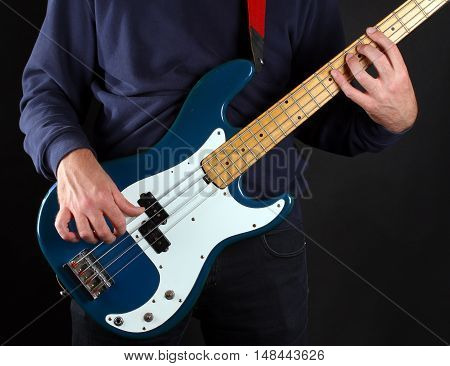 Musician playing his blue and white bass guitar