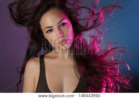 beautiful girl with pink back light in her long flying hair studio portrait
