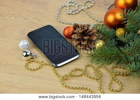 Festive greetings online. Xmas SMS. modern technologies.Modern Christmas present. Smartphone and branches of a Christmas tree on a wooden background.