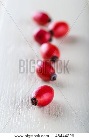 Several Red Hips In A Row Placed On White Wooden Board