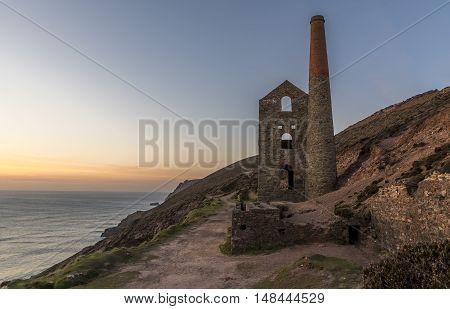 Derelict Cornish tin mine, on the cliff edge, at sunset