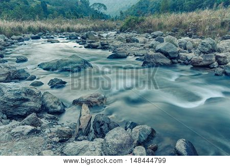 Beautiful Reshi River water flowing through stones and rocks at dawn Sikkim India. Blue tinted image. Reshi is one of the most famous rivers of Sikkim flowing through the state and serving water to many local people.