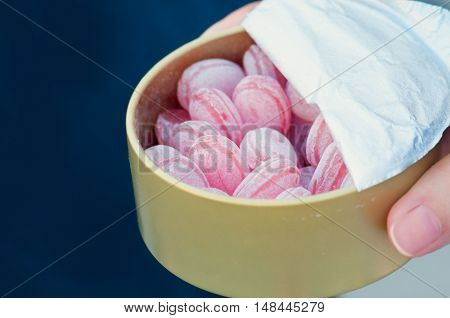 adult a child pink candy treats in powdered sugar from a metal box
