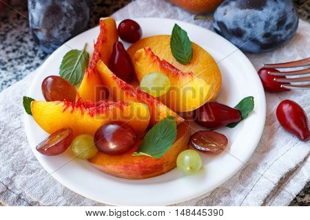 Fruit Salad In White Plate. Snack Of Fresh Peaches, Grapes, Dogwood, Plums, And Mint Leaves. Healthy