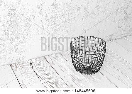 Vintage wire basket on white wooden rustic floor industrial wicker storage bin