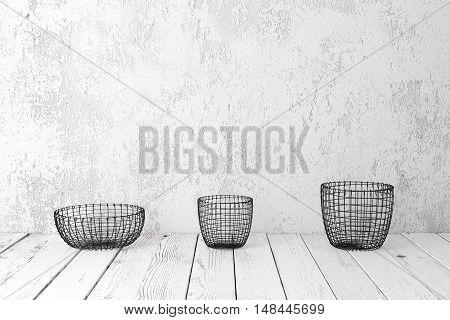 Vintage wire baskets on white wooden rustic floor industrial wicker storage bins