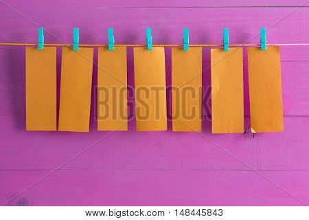 Blank Orange Note Pad Sheets Hanging From String