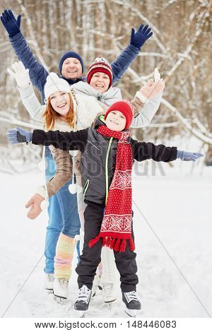 Smiling family of four stands on skates on ice pathway in winter park spreading arms to sides.