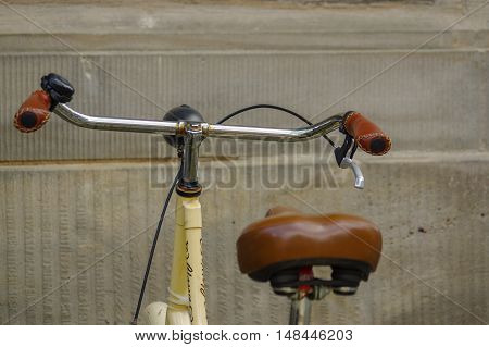 detail of old yellow bicycle. leather seat with shock absorbers and wheel