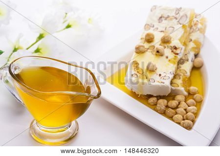 Honey in a saucepan and poured honey candy and nuts on a white plate
