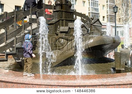 Tobolsk, Russia - May 2, 2010: Children play on Wonderful yudo Fish whale Fountain near Kremlin
