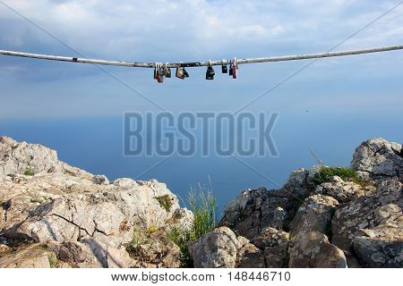 multiple padlocks hung on the metal pipe to the memory on sky background on top of rocky mountain