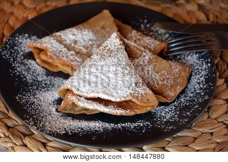Sweet homemade pancakes with jam and icing sugar.